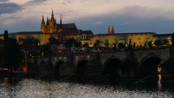 Karlův most a Pražský hrad za soumraku jako město světla přicházejí