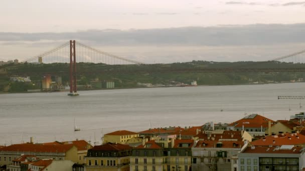 Elevated telephoto clip of 25th April bridge and small yachts sailing Tagus river in Lisbon, Portugal