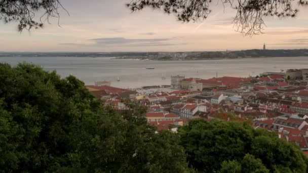 View of ferry crossing Tagus river towards Lisbon framed by trees. Taken from Sao Jorge Castle during evening hours