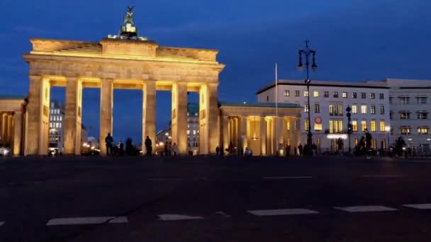 Nachtaufnahme des Brandenburger Tors in Berlin im Tiefflug, als der Abendverkehr vorbeiströmt.