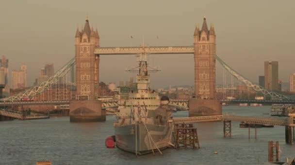 Dlouhý statický klip HMS Belfast zarámovaný Tower Bridge v Londýně. Pořízen při západu slunce v jarním večeru