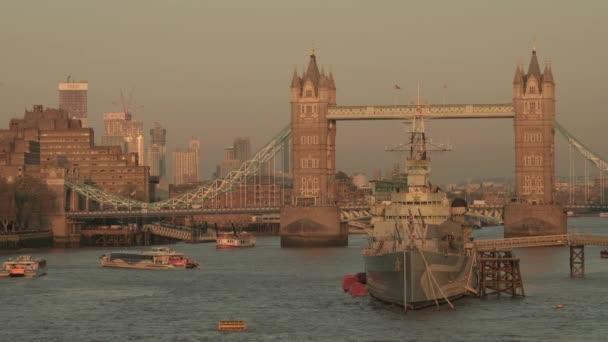 Statické video z bazénu v Londýně s HMS Belfast a Tower Bridge v Londýně jako říční autobusy plující podél řeky Temže. Pořízen za soumraku za jarního večera