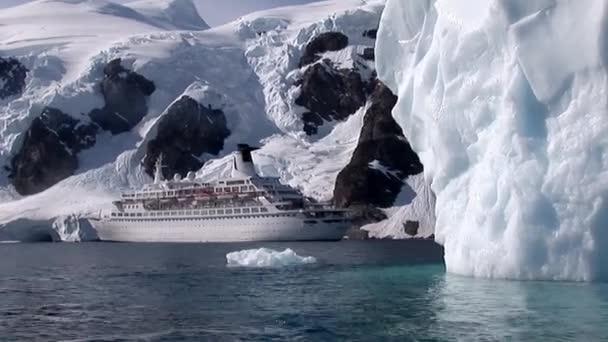Clip eines Kreuzfahrtschiffes vor schneebedeckten Bergen während eines sonnigen Tages im Hafen von Neko, Antarktis