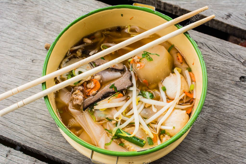 TOM YAM pork noodle soup In a bowl, along with the chopsticks on