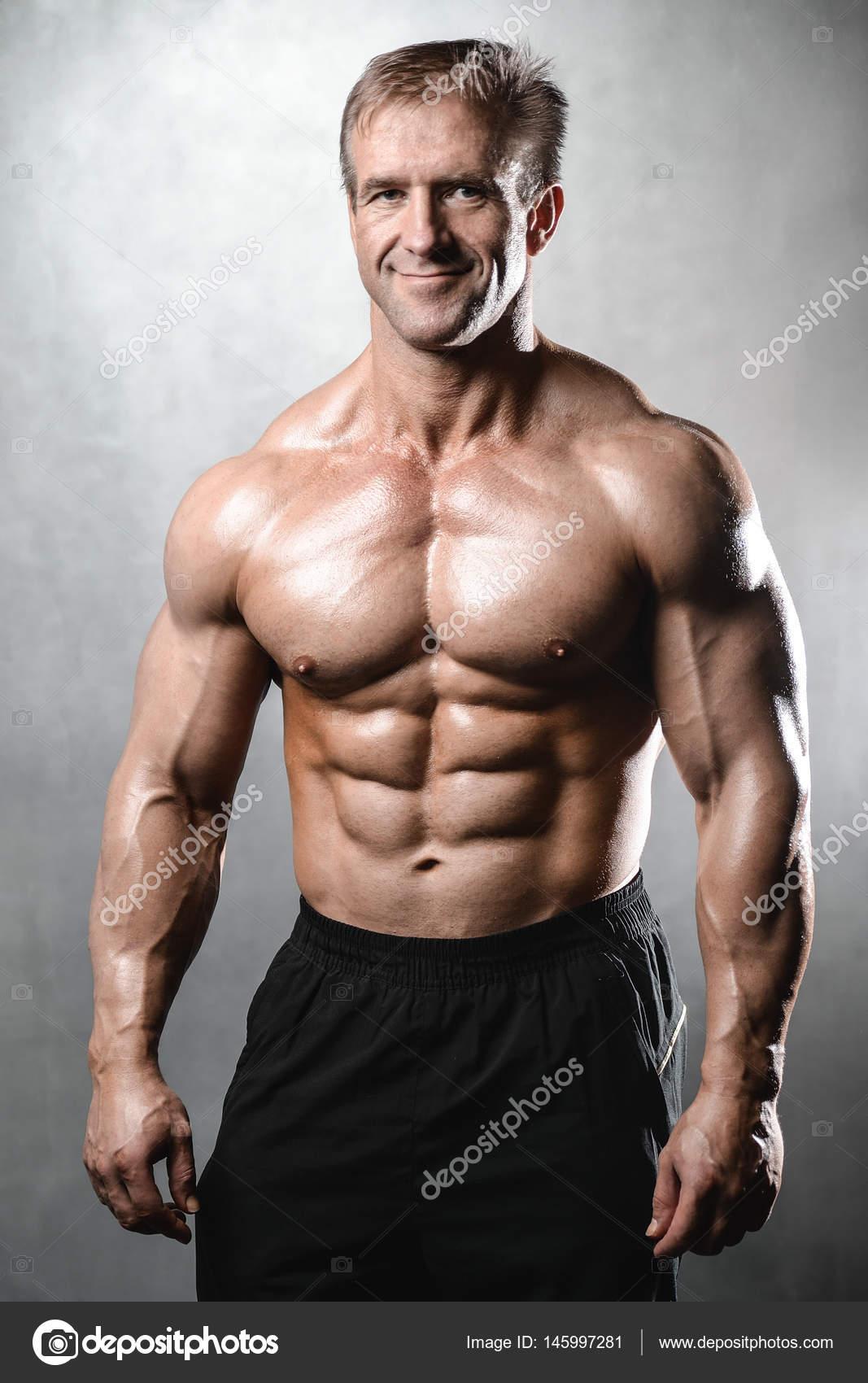 Brutal stark bodybuilder alter mann posiert im studio grey