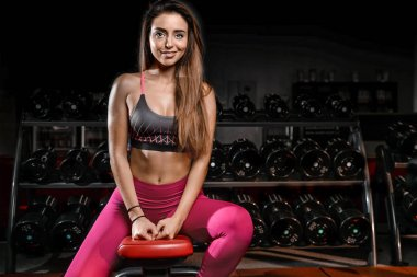 Girl execute exercise with dumbbells