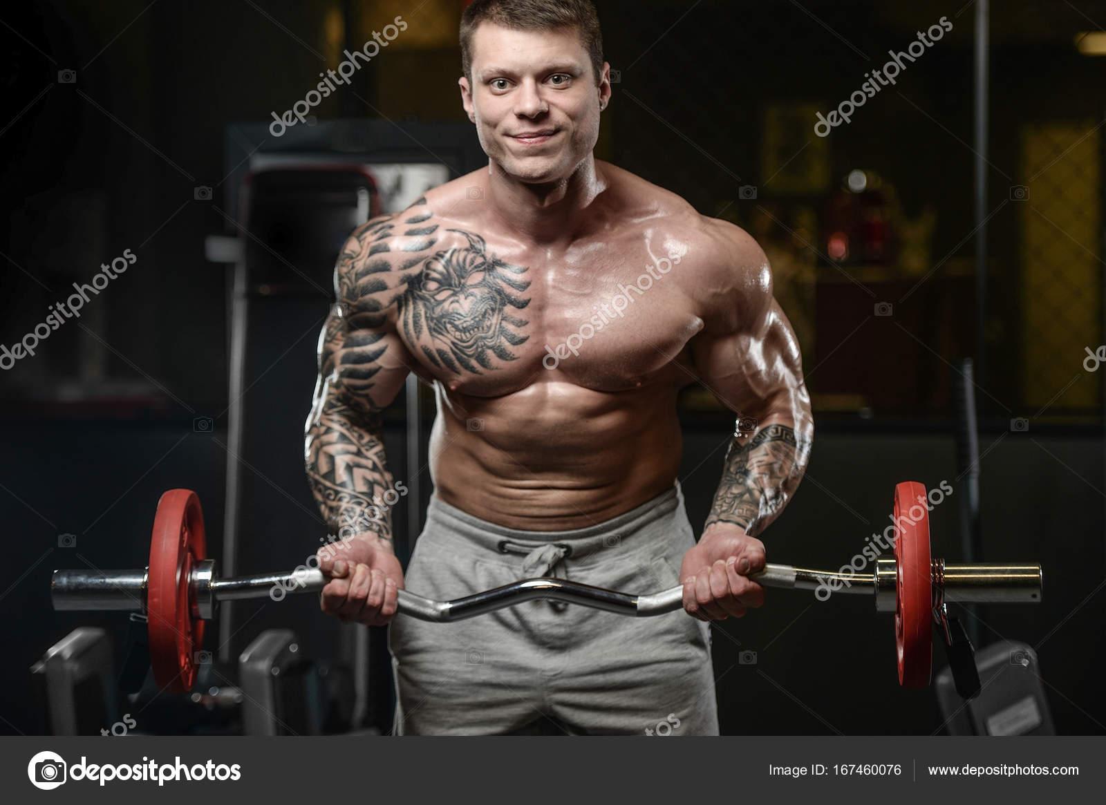 Silne I Przystojny Sportowe Tatuaż Młody Człowiek Z Mięśni Zdjęcie