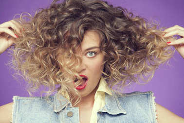 Portrait of curly haired woman making faces at camera