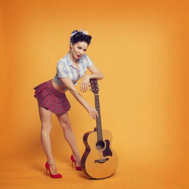 beautiful girl in retro style with the guitar on a yellow background