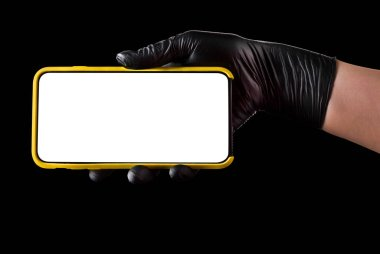 Hand in black glove holding mobile phone with blank screen on black background. Isolated with clipping path.