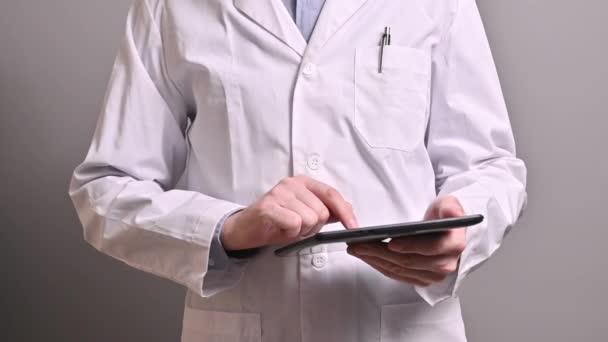 Kaukasischer Arzt in weißem Mantel mit Tablette