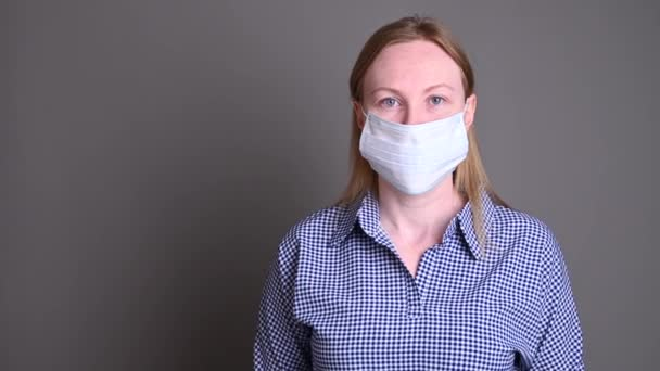 Young woman in blue gloves take off a medical mask and looking at the camera