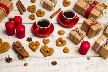 Two red coffee cups, cookies in the shape of a heart and gifts