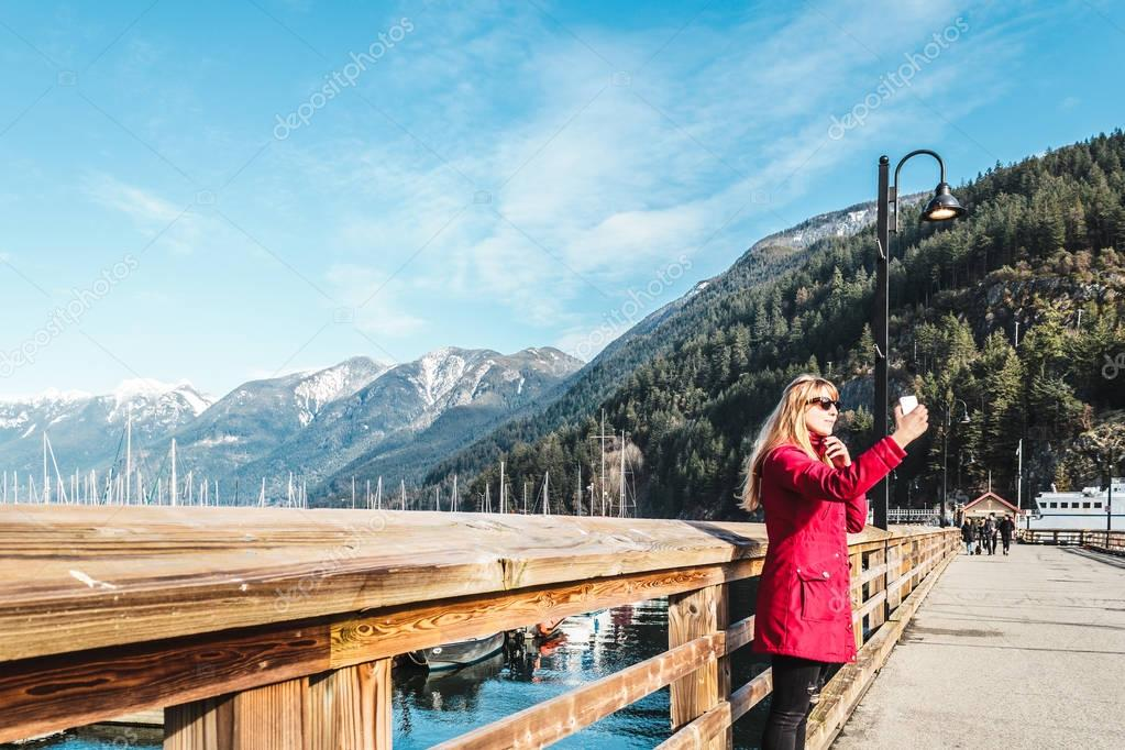 Girl taking selfie at Horseshoe Bay in West Vancouver, BC, Canad
