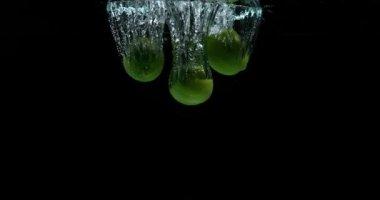 Zelené citrony, citrus aurantifolia, ovoce pádu do vody proti černé pozadí, Slow Motion 4k