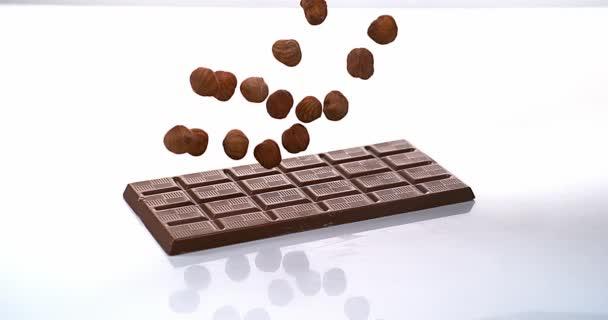 Lískové ořechy spadající na tabletu mléčná čokoláda