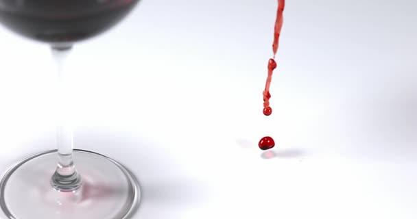 Rotwein wird in der Nähe eines Glases ausgeschenkt