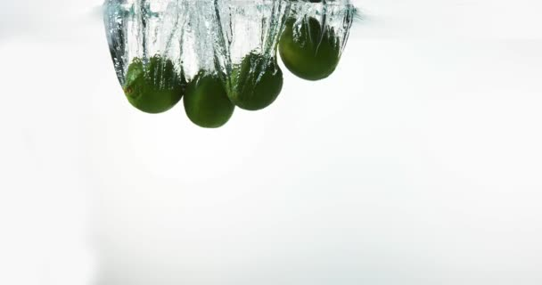 Zelené citrony, citrus aurantifolia,, ovoce pádu do vody proti bílé pozadí, Slow Motion 4k