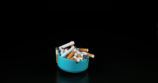 Aschenbecher und Zigaretten fallen vor schwarzem Hintergrund, Zeitlupe 4k