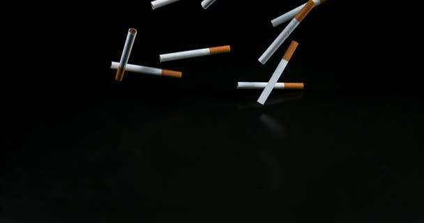 Zigaretten fallen vor schwarzem Hintergrund, Zeitlupe 4k