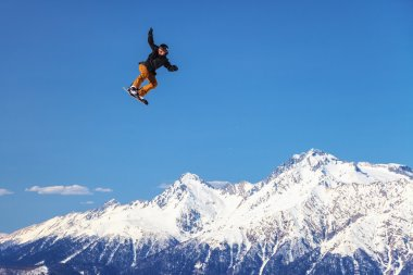 Male snowboard rider flying from a ski jump on snowy mountain background