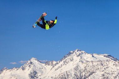 Snowboard rider flying from a ski jump