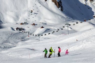 Group of skiers standing on mountain cirque ski slope at sunny day against the chair lifts background