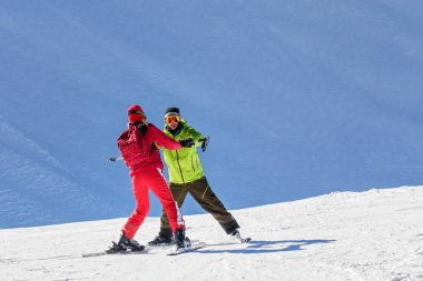 Male instructor teaches skiing to a young woman on a sunny day on snowy slope background