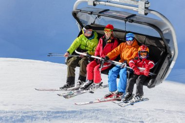 Family of four people riding on a chair ski lift