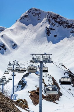 Vacant cableway lift chairs of an empty ski resort at sunny winter day on a snowy mountain peak vertical background