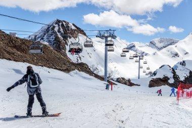 Snowboarder standing on snowy mountain slope in Sochi Krasnaya Polyana ski resort