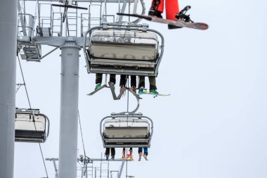 Legs of ski and snowboard riders on a cable chair lift in cloudy snowy winter mountains scenic close up