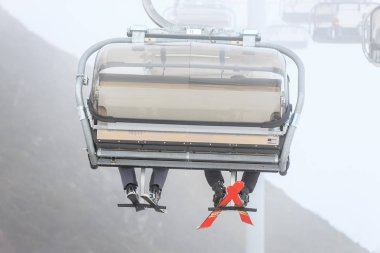 Legs of two ski riders climbing on a cable chair lift in cloudy snowy winter mountains close up