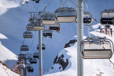 Cableway chair lifts with skiers and snowboarders on blue sky background