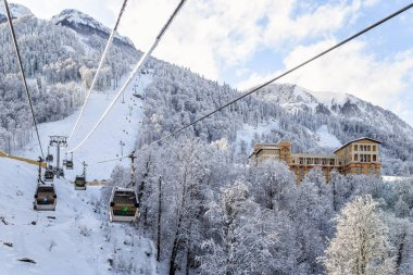 Cableway sli lift cabins on blue sky and snowy mountain background beautiful winter scenery