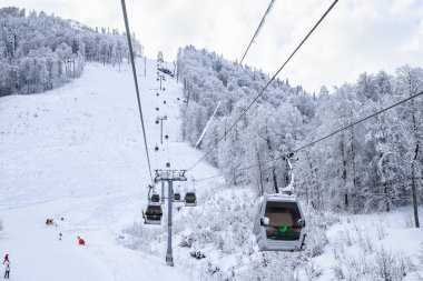 Cableway lift cabins on snowy mountain background beautiful winter scenery