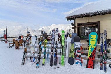 Skis and snowboards are leant against a winter cafe fence