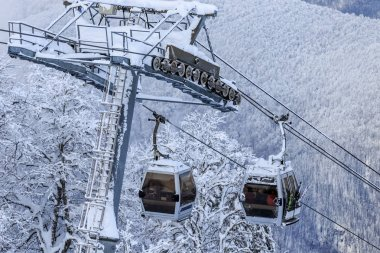 Cableway ski lift cabins on snowy mountain background beautiful winter scenery