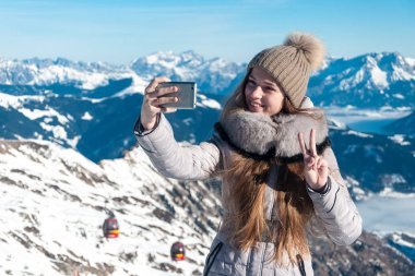 young beautiful girl photographed themselves on the phone in the winter in the mountains