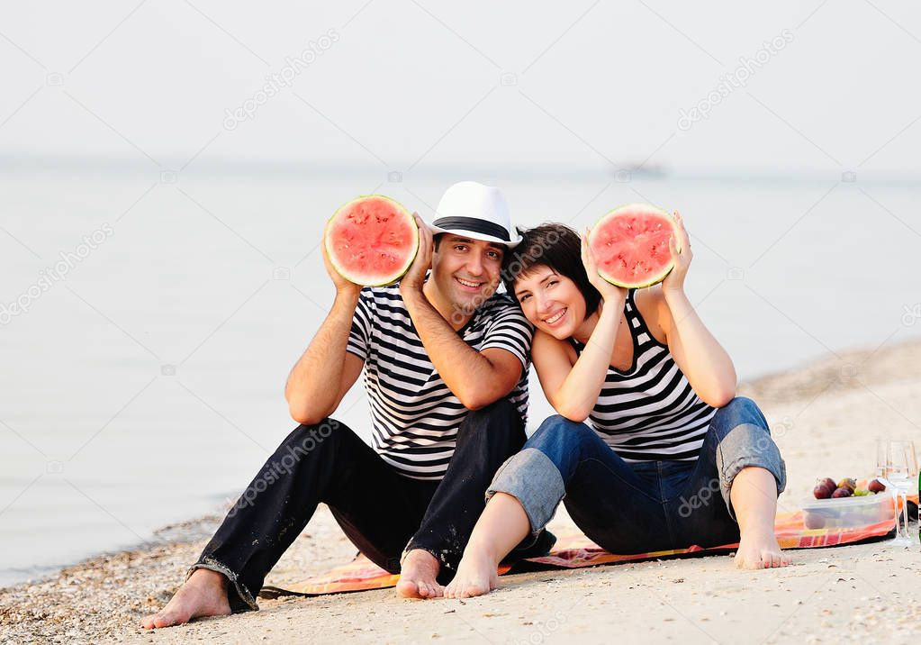 couple sitting on beach with watermelon