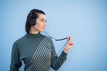 Beautiful woman in headphones on blue wall background in gray dress