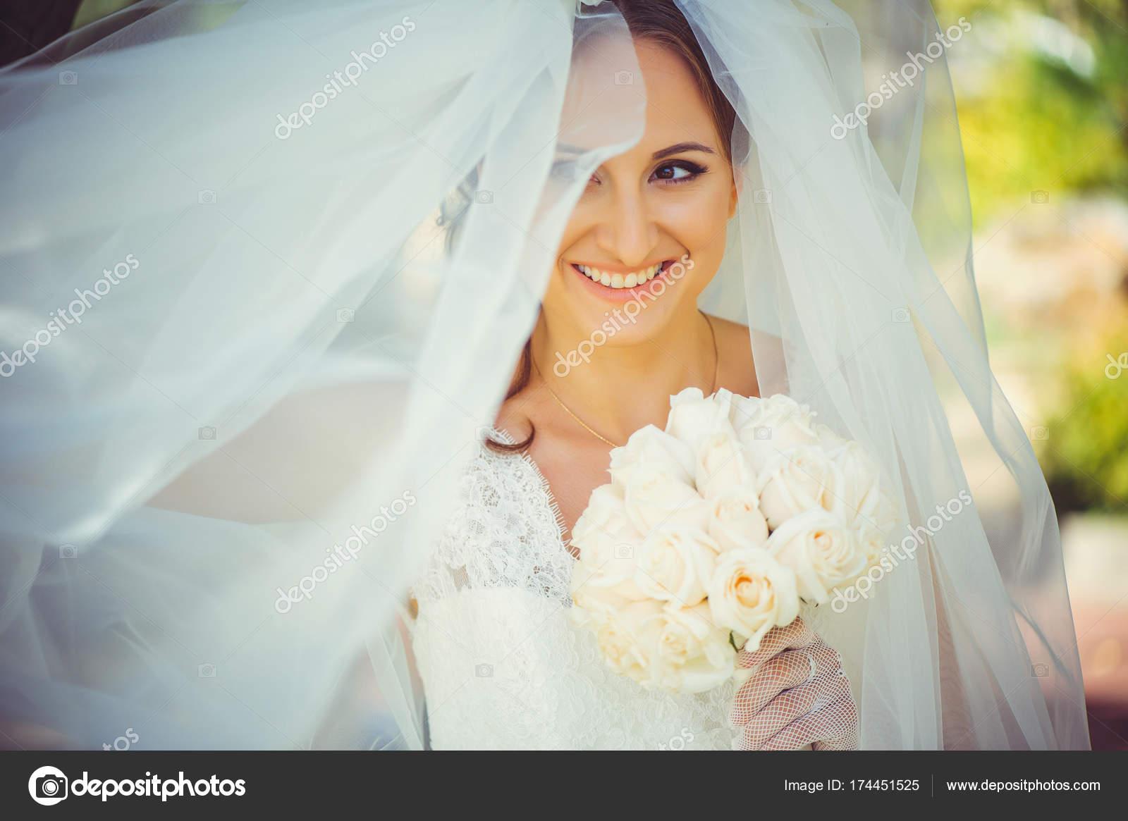 tierna novia feliz en velo, feliz mujer en vestido de novia con ramo ...
