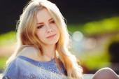 fiatal nő ül a gyep átgondolt haj játszik gyönyörű szőke egyenes hosszú nap.