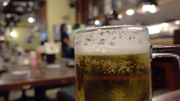 Hideg japán sört Izakaya háttérrel.