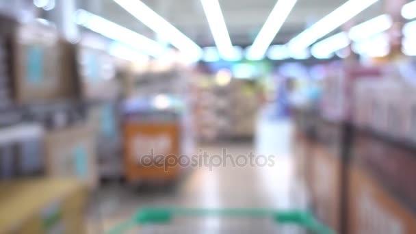 Nákupní košík pohybuje zrychleně rozostření v supermarketu