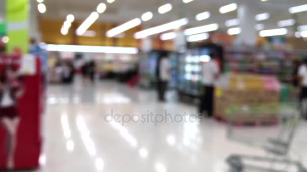 Blurred shot of consumers in supermarket from shopping cart