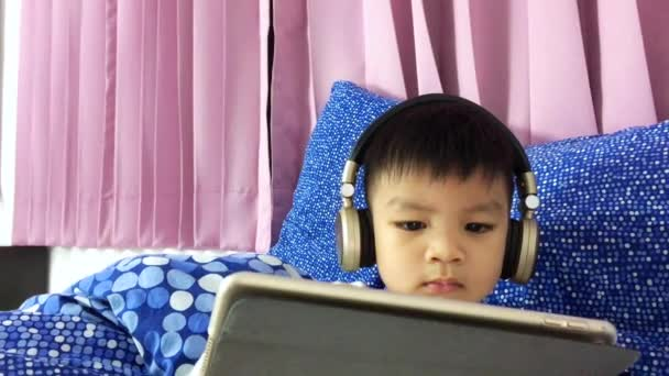 Asian child is wearing a headphone and watching cartoon on his tablet.
