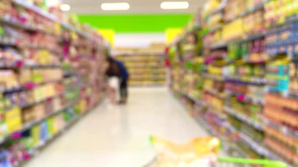 Rozmazaný záběr spotřebitelů v supermarketu z nákupního košíku