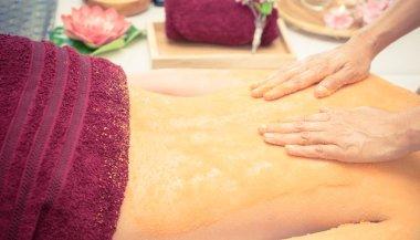 Spa Therapist is scrubbing customer back with orange salt