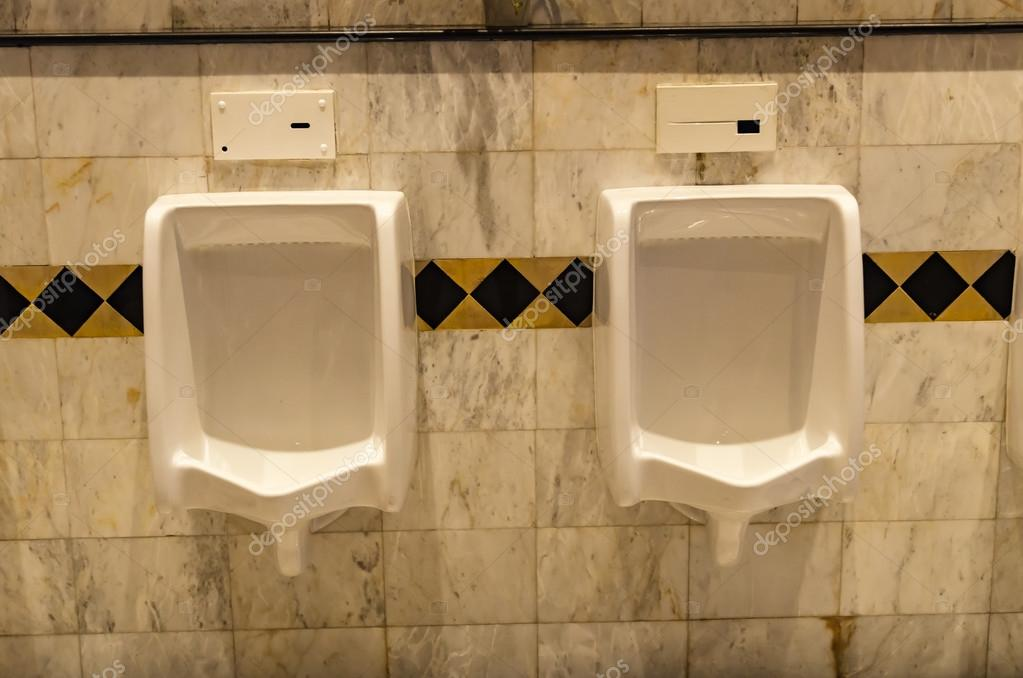 Muro di piastrelle nel cesso di uomo con wc vista di orinatoi e